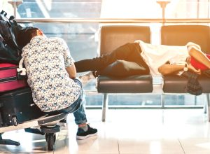two travelers sleep in an airport