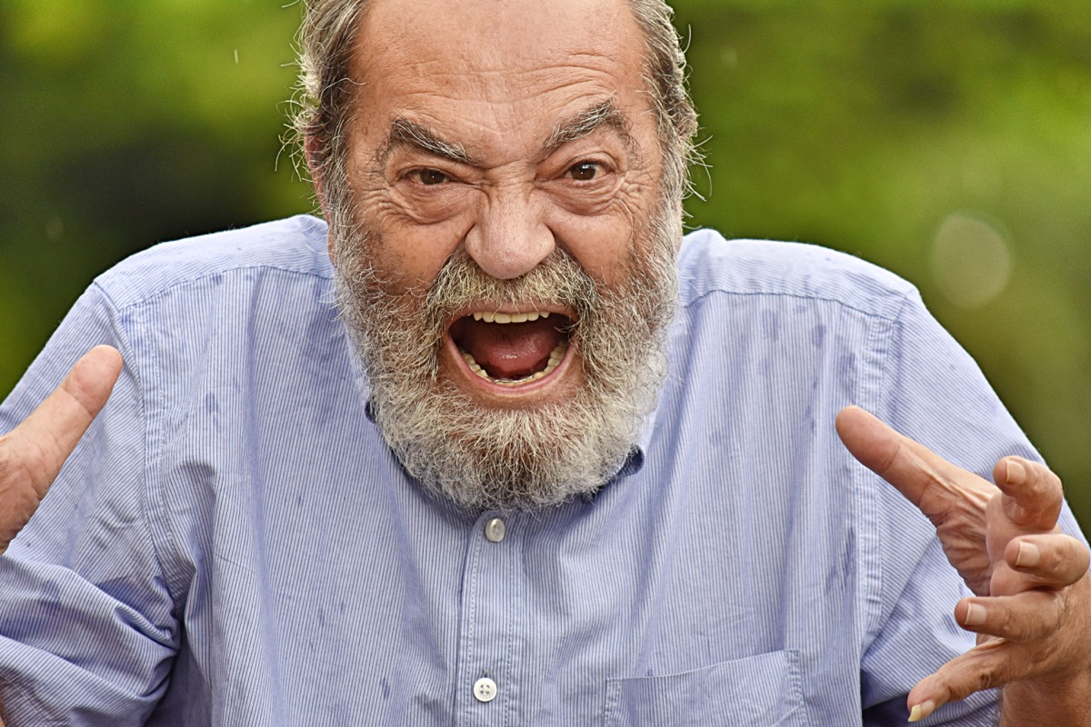 Angry older man yelling at someone or something