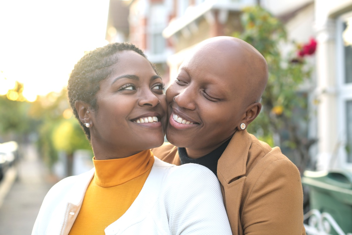 30-something black lesbian couple being affectionate outdoors