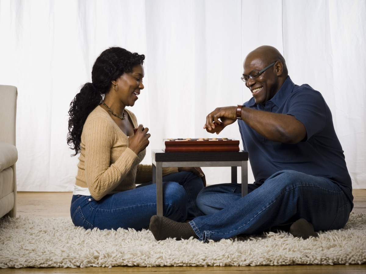 middle aged black couple playing board game on floor