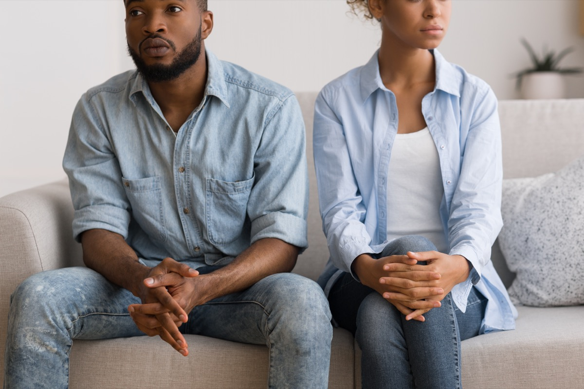 young black woman and man sitting on couch looking upset