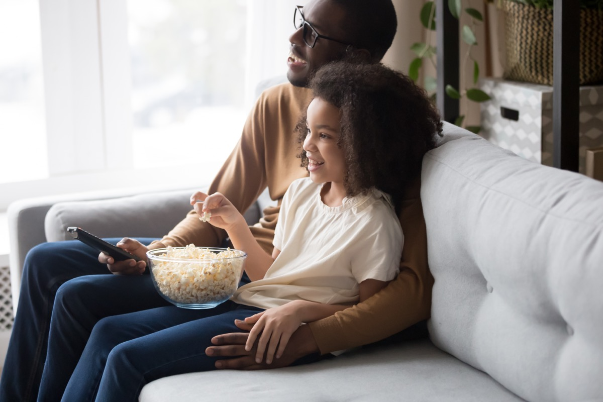 father and daughter watching movie