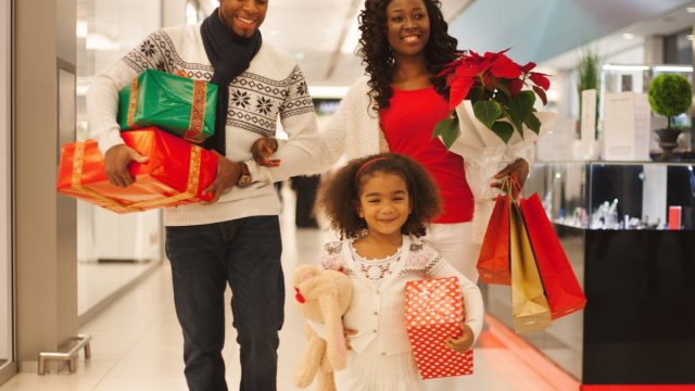 30-something black mother and father and young daughter shopping for holiday gifts at a department store or mall