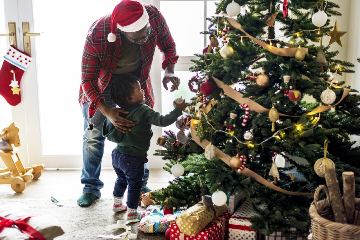 young black father and toddler son decorating christmas tree
