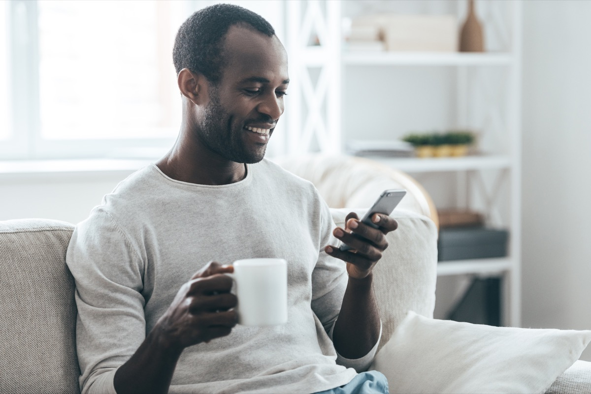 middle aged black man texting on couch with cup of tea