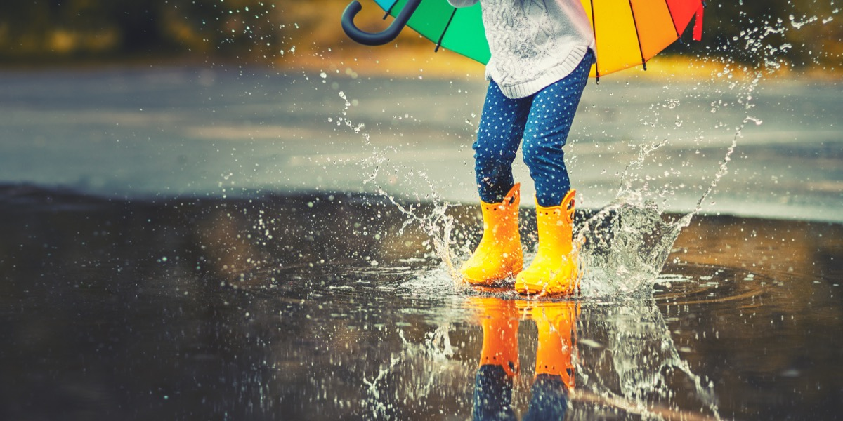 child jumping in puddle on a rainy day