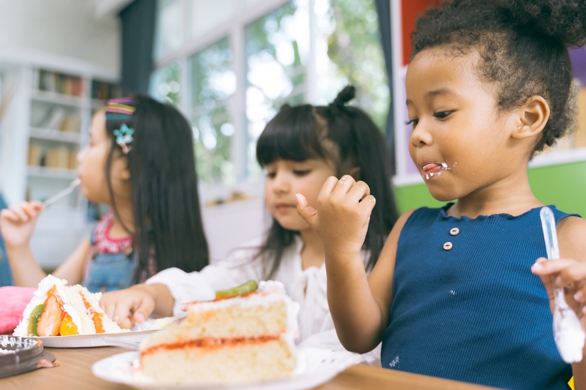 a bunch of children eating cake