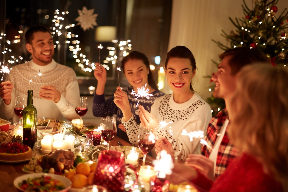 young people gathered around the christmas dinner table, holding sparklers