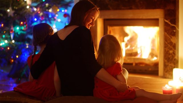 mom and her two daughters watching the fireplace in the living room