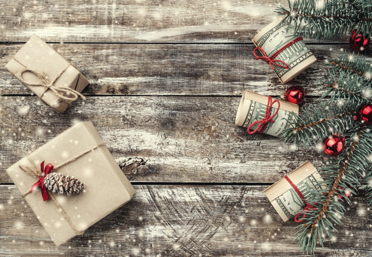 christmas gifts and money on wooden background