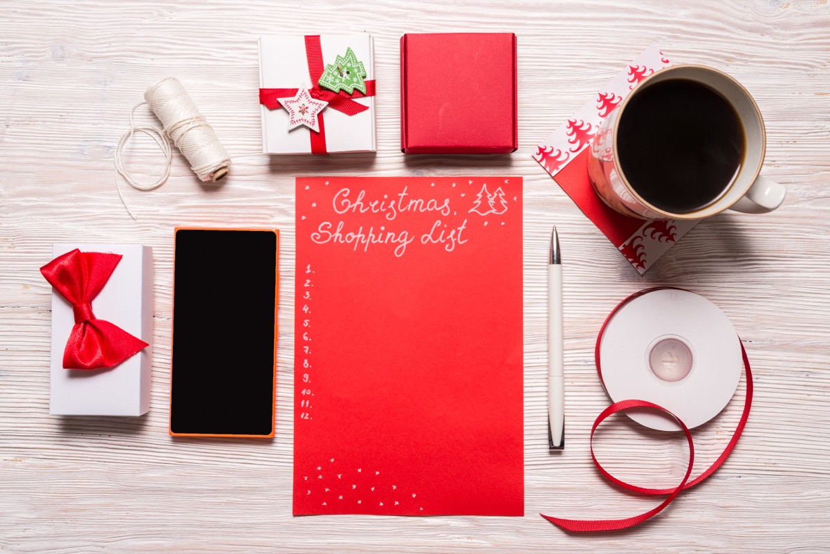 christmas shopping list with gift boxes and coffee cup on table