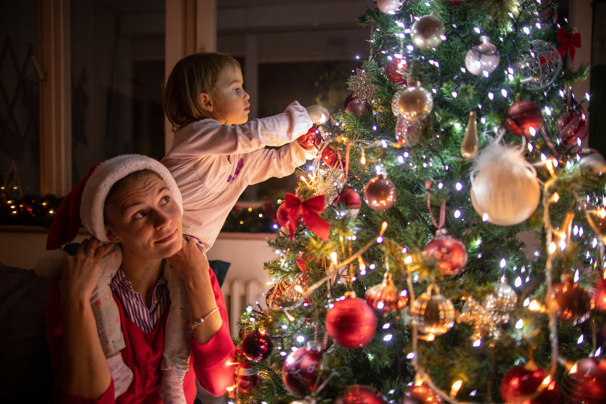 Mother carrying her daughter on shoulder while decorating the Christmas tree