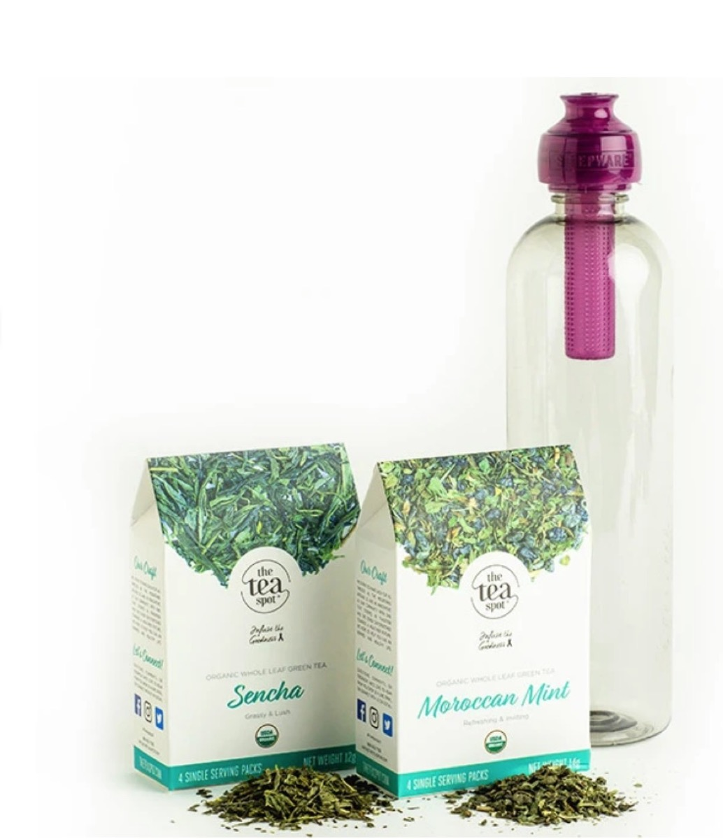 two cardboard containers of tea and water bottle with purple spot
