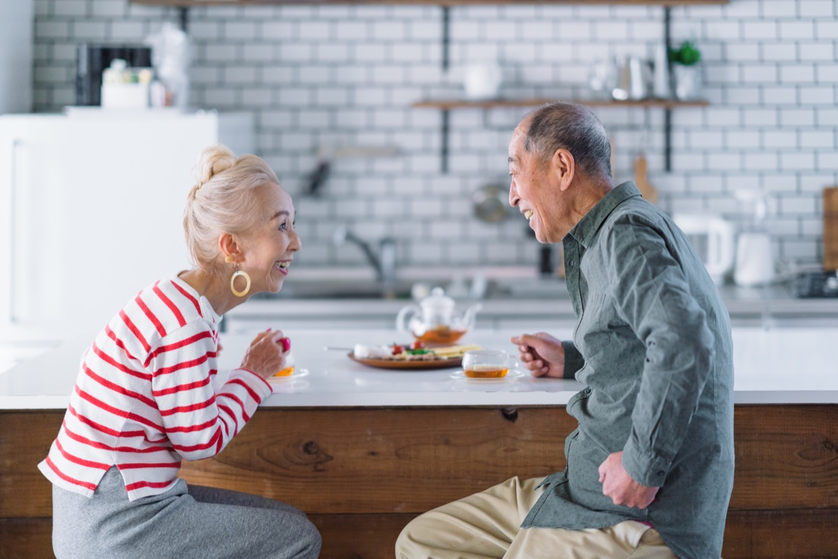 an older couple making eye contact with each other in their kitchen