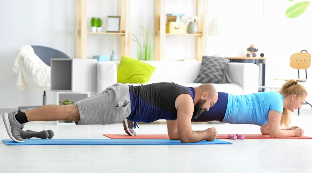 Couple doing planks together in their living room