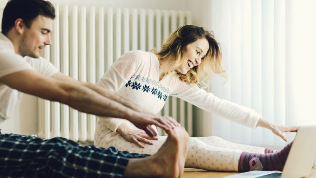 Happy couple doing stretches and working out at home