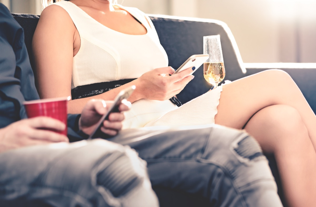 white couple texting on couch