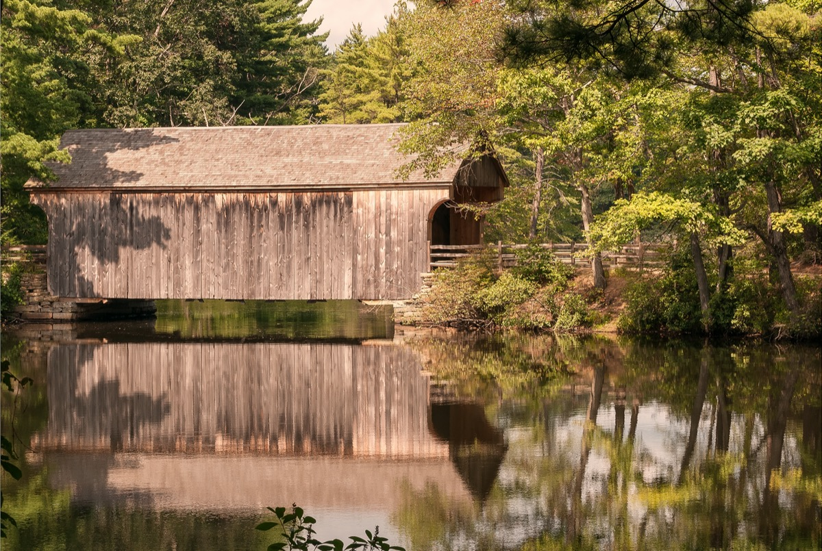 covered wooden bridge reflecting in water