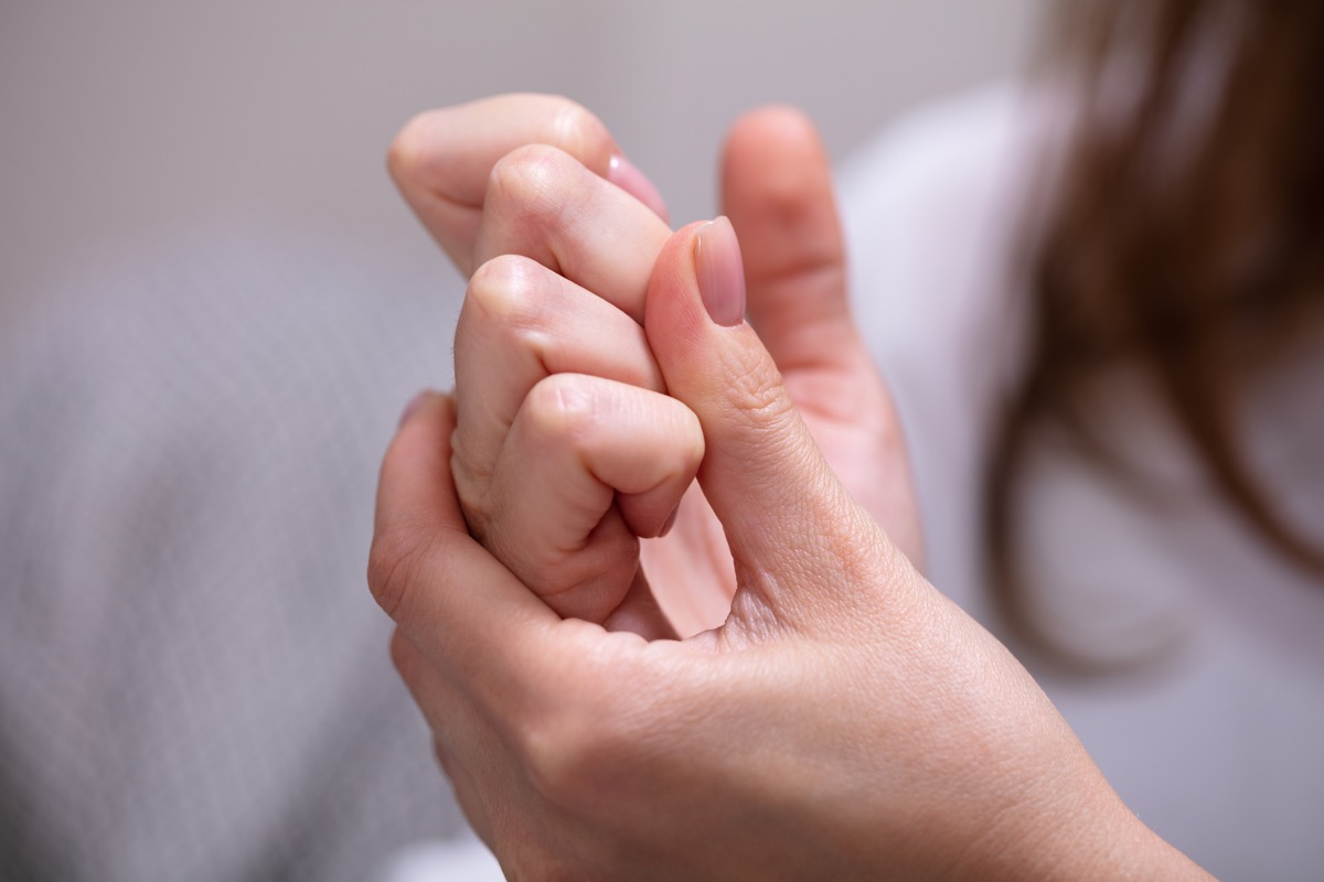 woman cracking her knuckles at home