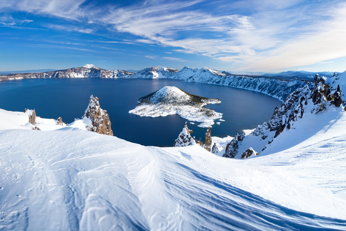 snowy mountains surrounding a lake and island