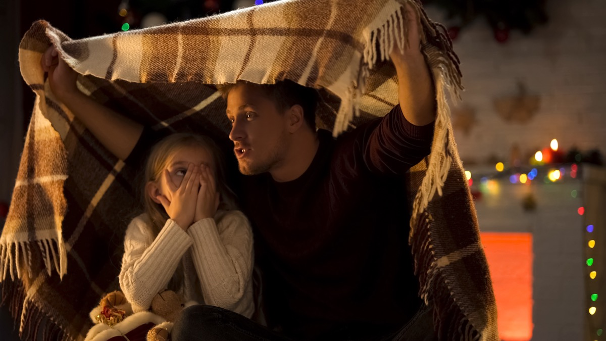dad telling scary christmas stories to daughter