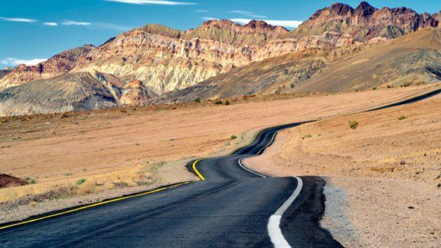desert road leads into cliffs in california