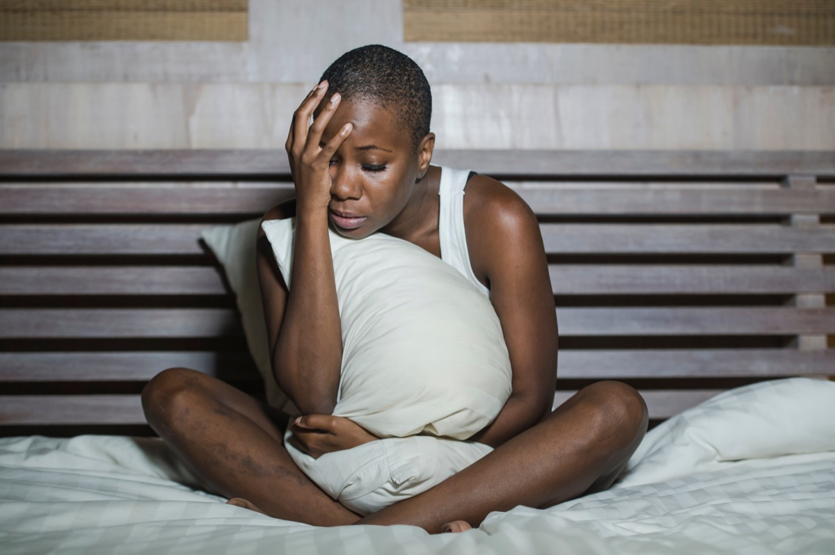 depressed woman sitting in bed