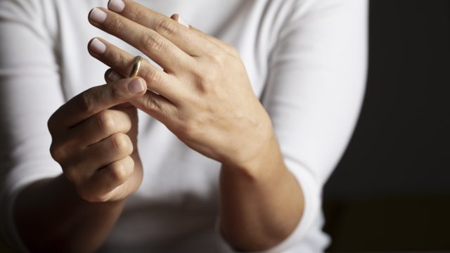 hands of white woman who is about to taking off her wedding ring.