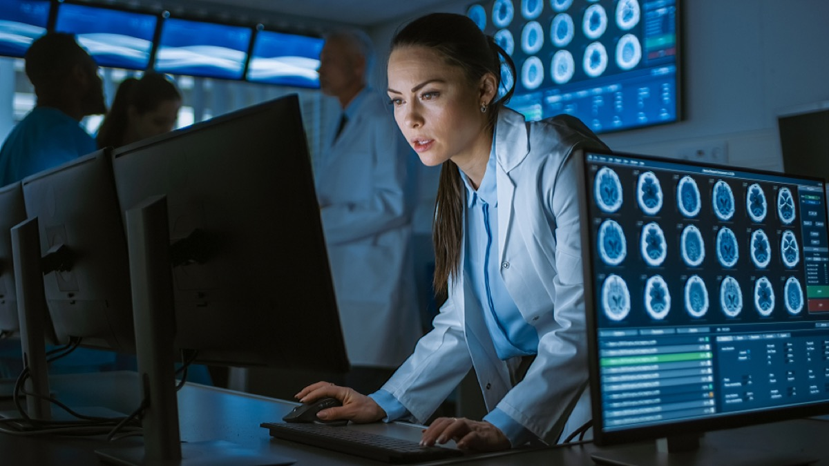 young female doctor in lab coat looks at scans