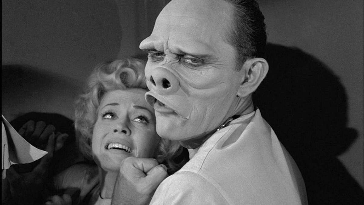 frightened woman cowering from monstrous deformed face on the twilight zone