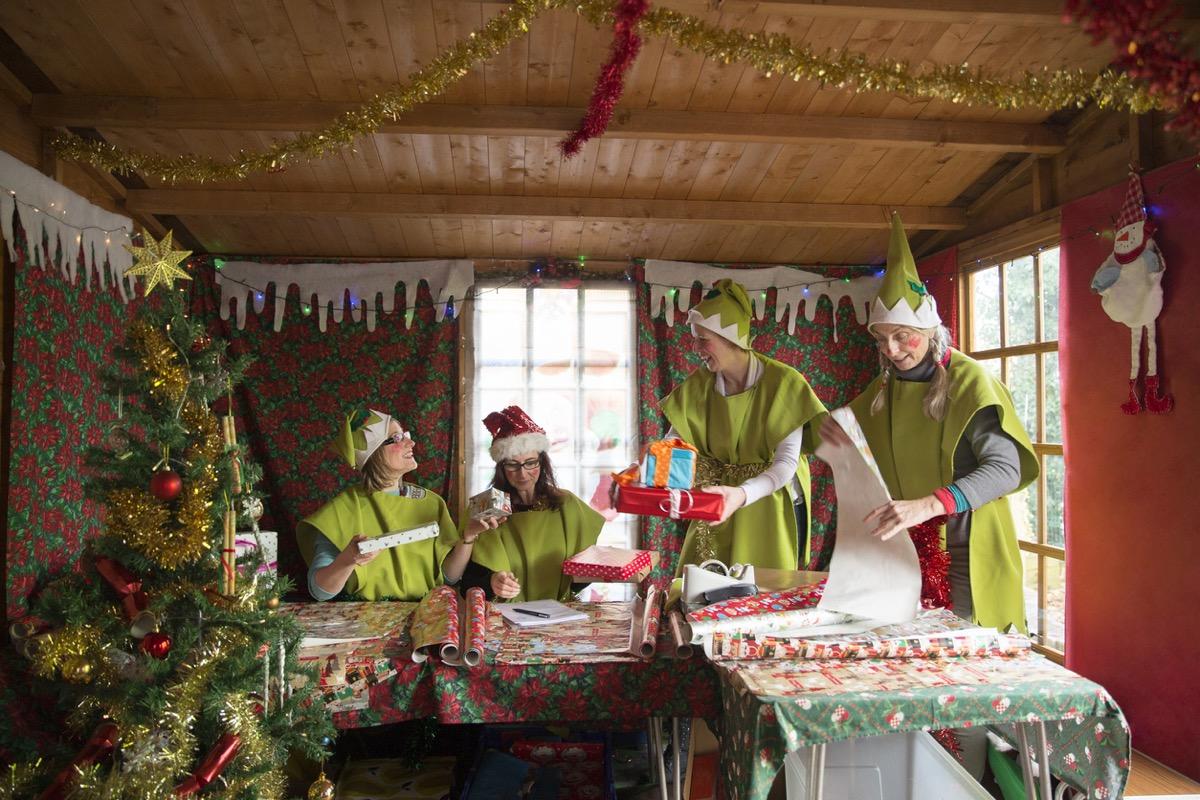 Four women dressed as Santa's elves wrap presents for Christmas.