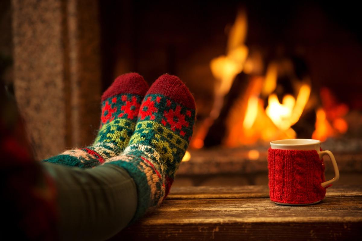 feet in woollen socks by the christmas fireplace