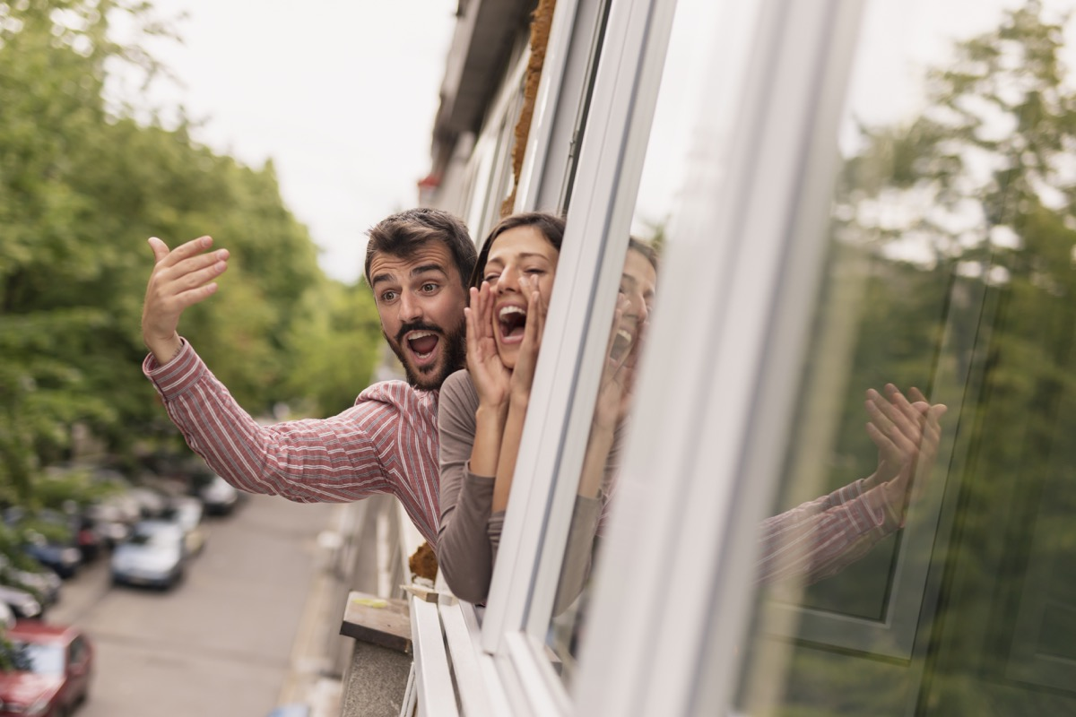 couple waving and shouting out of window in their house
