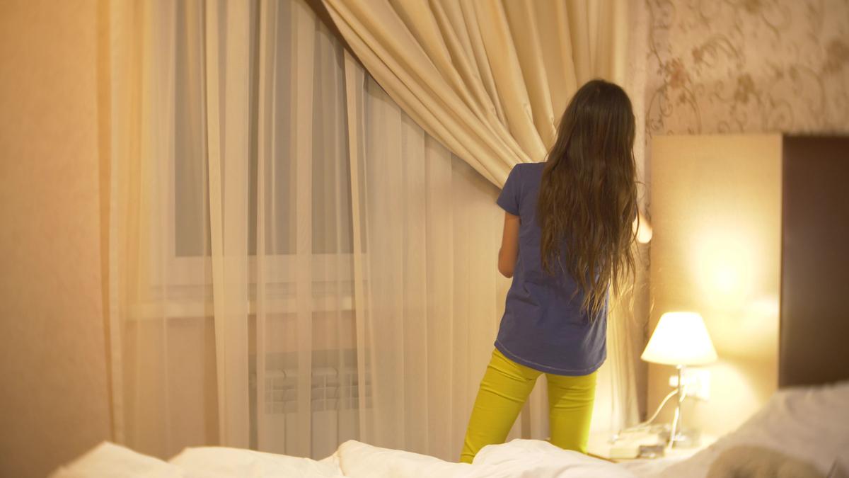 girl closing curtains of bedroom at night