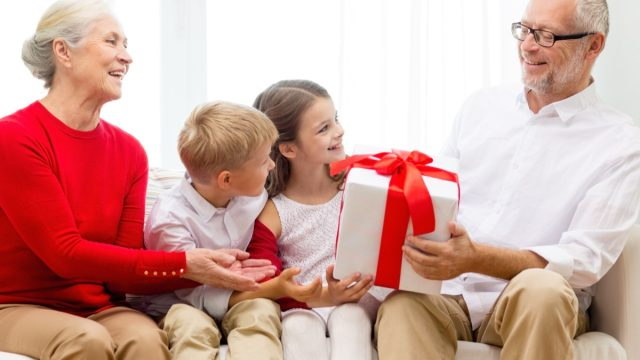 white grandparents getting gifts from their two grandkids on couch