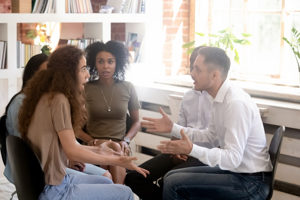 group apologizing and arguing with woman overlooking