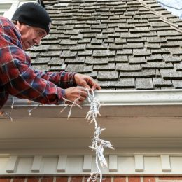 Man using a ladder to hang up Christmas lights