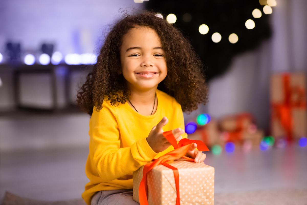 happy little girl opening gift