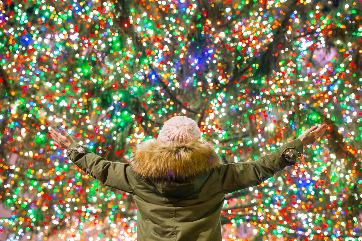 happy woman in front of rockefeller center tree