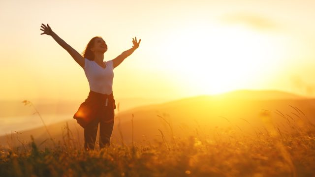 happy woman in nature at sunset