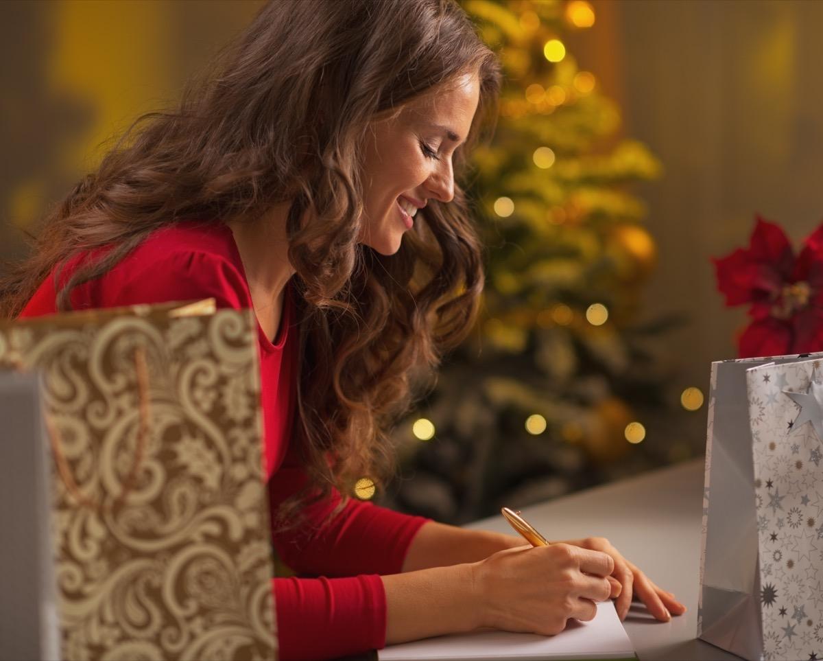happy woman writing christmas list