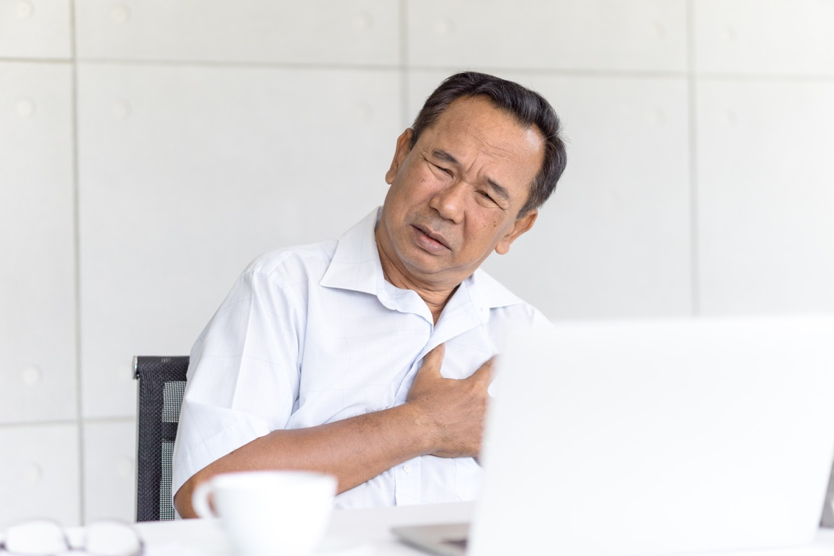 Man sitting at a desk clutching his heart and chest in pain
