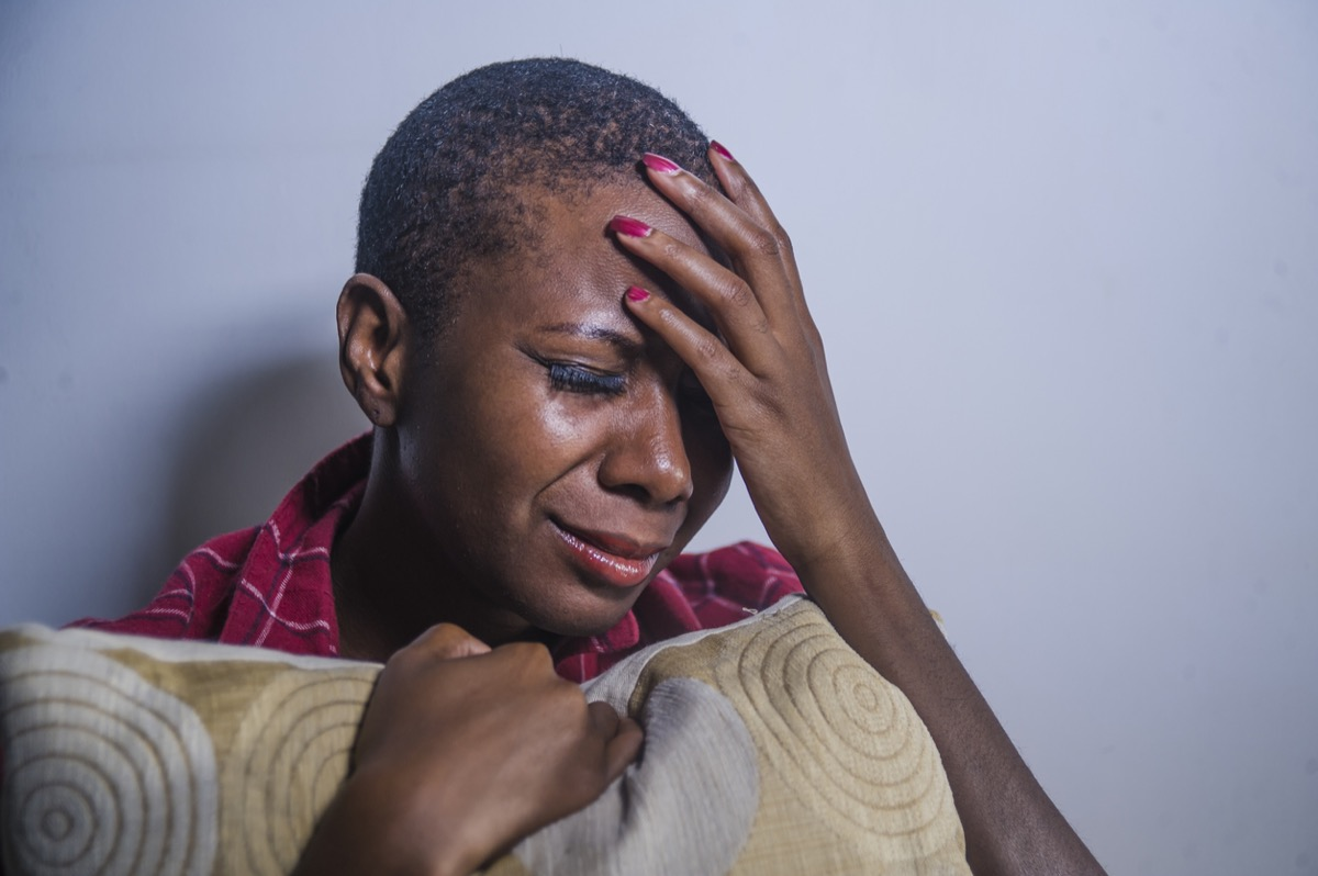 black woman crying and clutching a pillow