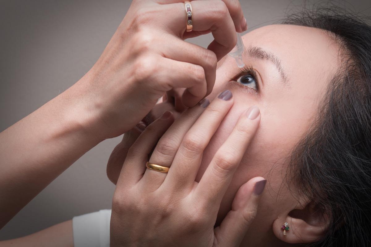 asian woman putting in eye drops