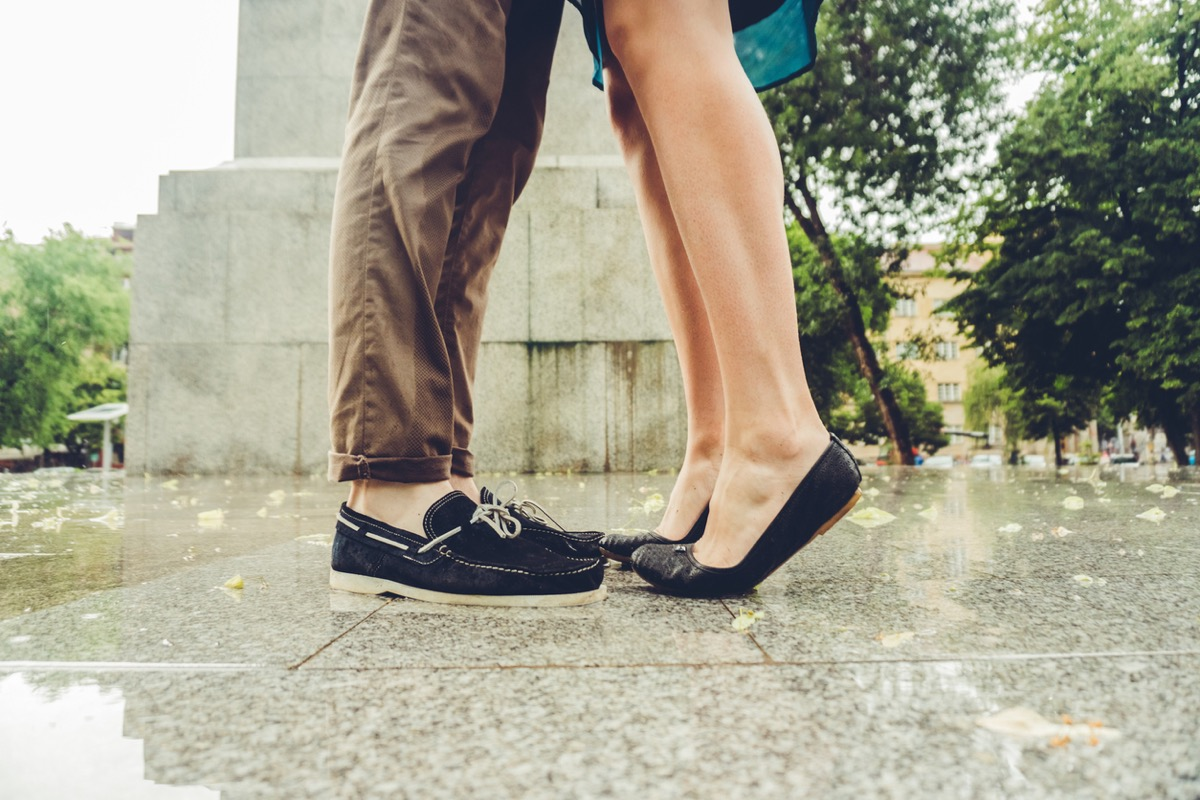 feet of woman on tiptoes to kiss man
