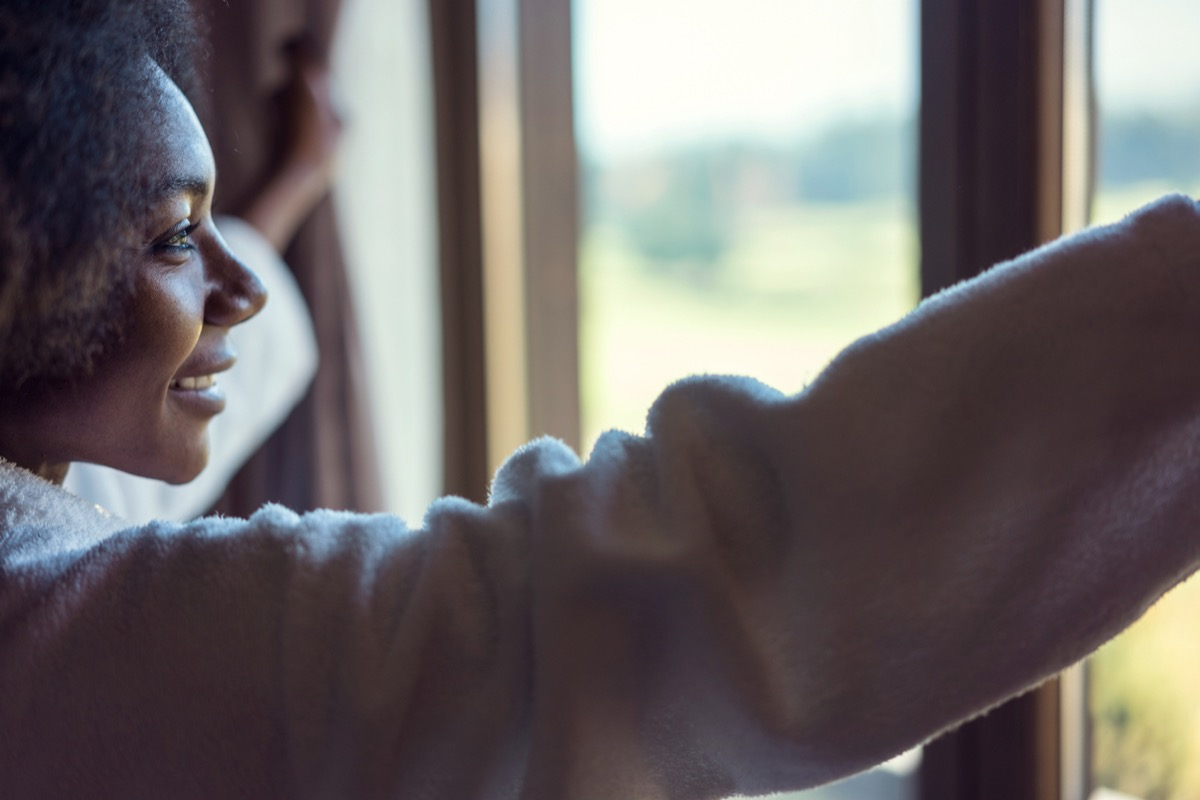 young black woman looking out the window and smiling in the morning