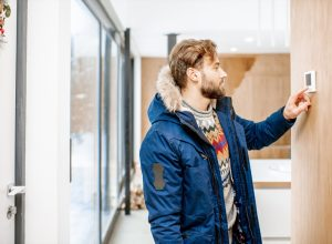 young white man in a winter coat adjusting the thermostat in his home