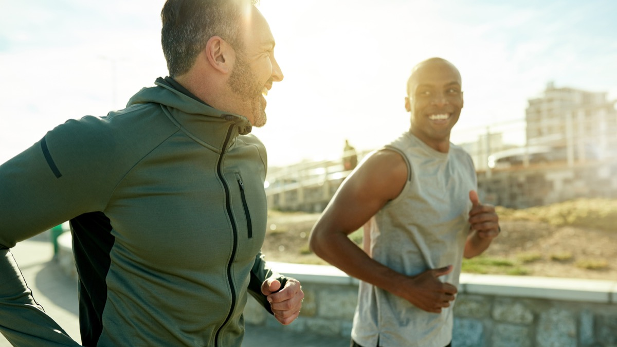 white man and black man running outside and smiling at each other
