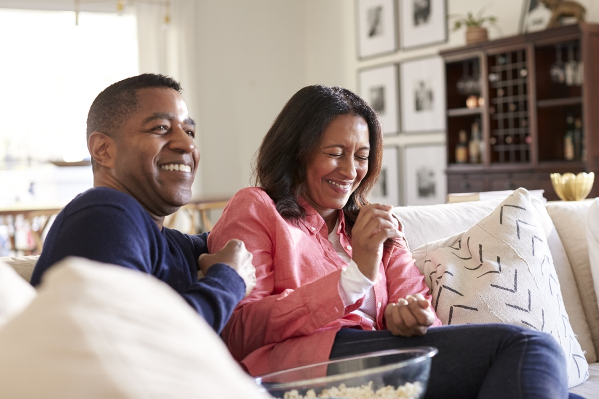 middle aged black couple laughing and eating popcorn on the couch
