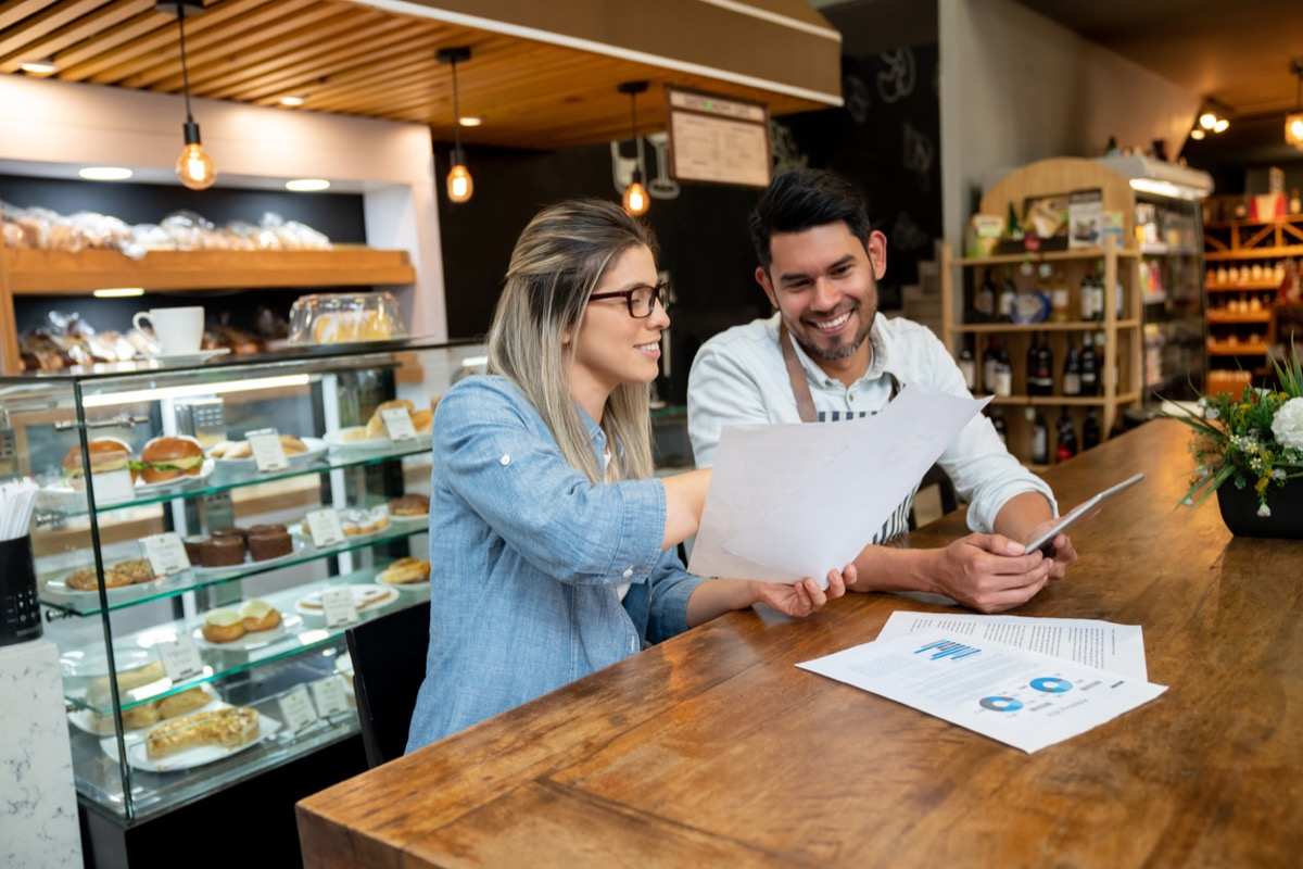 white woman at bakery showing a paper to younger latino employee